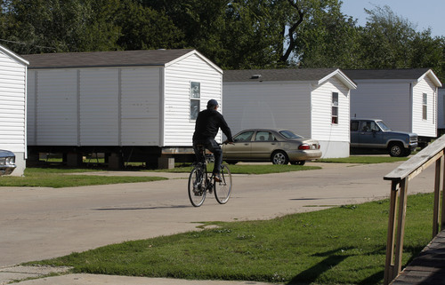 A resident rides a bicycle on the grounds of Hand Up Ministries in Oklahoma City, Wednesday, Oct. 3, 2012. Hand Up Ministries is a non profit faith-based organization that offers help to men and women coming out of the prison system to re-enter society. The grounds currently house 150 sex offenders and 7 other felons. (AP Photo/Sue Ogrocki)