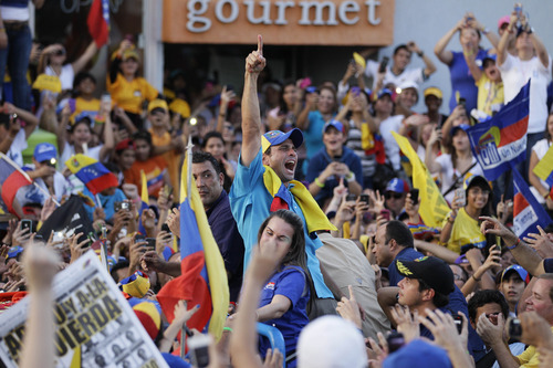 Opposition presidential candidate Henrique Capriles, center, gestures from the top of a vehicle during a campaign rally in Maracaibo, Venezuela, Wednesday, Oct. 3, 2012. Capriles will run against President Hugo Chavez in the presidential elections Oct. 7. (AP Photo/Ariana Cubillos)