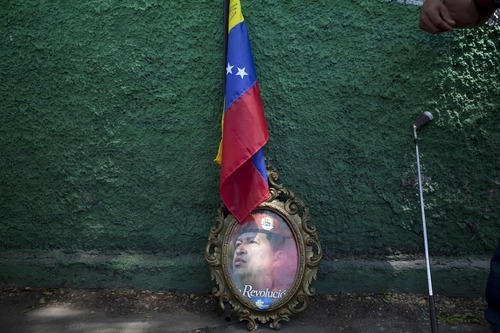 An image of Venezuela's President Hugo Chavez sits under a Venezuelan flag next to a golf club during a campaign rally in Maracay, Venezuela, Wednesday, Oct. 3, 2012. Chavez is running for re-election against opposition candidate Henrique Capriles in presidential elections on Oct . 7. (AP Photo/Rodrigo Abd)