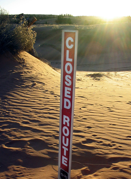 Associated Press file photo | A sign warns off-roaders to stay away from a stretch at the Coral Pink Sand Dunes in 2004. Kane County is opposed to a U.S. Fish and Wildlife proposal to designate 2,200 acres of the Coral Pink Sand Dunes as critical habitat for the tiger beetle species that lives there, saying the designation will adversely impact tourism fueled by dune riding.
