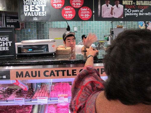 Dean Jitchaku, an apprentice meat cutter, hands a package of grass-fed beef to a customer at the Whole Foods Market Kahala store in Honolulu on Sept. 28, 2012. National trends in locally grown foods and grass-fed beef have caught on in Hawaii, but crushing drought has made it difficult for ranchers to keep enough cattle in Hawaii to capitalize on the demand. (AP Photo/Audrey McAvoy)