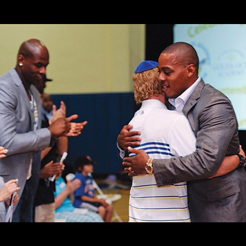 Utah Jazz guard Randy Foye hugs his longtime coach and mentor Sandy Pyonin at a Sept. 9 event honoring Pyonin in West Orange, N.J. Foye hosted the ceremony. Al Harrington of the Orlando Magic is in the background. Courtesy of Rob Stevens