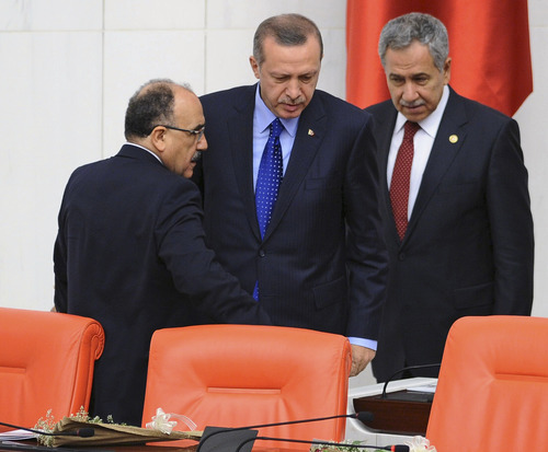 In this Monday, Oct. 1, 2012 photo, Prime Minister Recep Tayyip Erdogan, center, and his deputies Bulent Arinc, right, and Besir Atalay seen at Turkey's parliament in Ankara, Turkey.  Turkey fired on Syrian targets for a second day Thursday, Oct. 4, 2012, but said it has no intention of declaring war, despite tensions after deadly shelling from Syria killed five civilians in a Turkish border town. Turkey's Parliament, meanwhile, began an emergency session to discuss a bill authorizing the military to launch cross border operations in Syria. If approved, the bill could more easily open the way to unilateral action by Turkey's armed forces inside Syria, without the involvement of its Western and Arab allies.(AP Photo)
