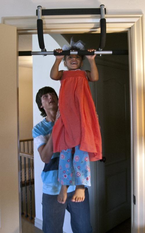Chris Detrick  |  The Salt Lake Tribune Nic Olsen, 16, helps his sister Lily Winchester, 4, do pull ups at their home in Draper Friday September 21, 2012.