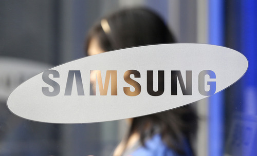 A visitor passes by the entrance way to Samsung Electronics Co. showroom at its headquarters in Seoul, South Korea, Friday, Oct. 5, 2012. Samsung Electronics Co. tipped all-time high quarterly operating profit, likely driven by strong sales of high-end smartphones that offset weak semiconductor orders. (AP Photo/Lee Jin-man)