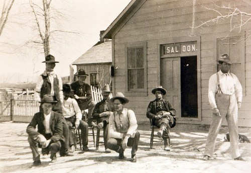 This is the saloon that was the hangout of The Wild Bunch in 1889. The man standing beside the tree is Harry Longbaugh (The Sundance Kid) and the man sitting on the chair beside him is Butch Cassidy. Courtesy of the Utah Historical Society