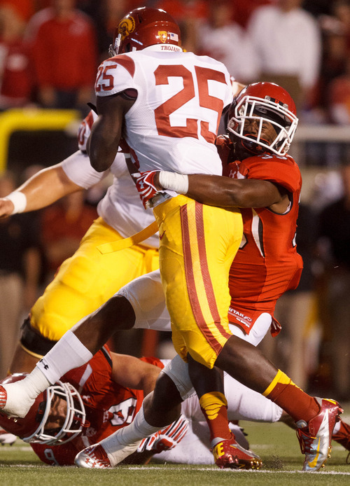 Trent Nelson  |  The Salt Lake Tribune Utah linebacker Reshawn Hooker (35) pulls down USC's Silas Redd during a game Oct. 4, 2012 at Rice-Eccles Stadium in Salt Lake City.