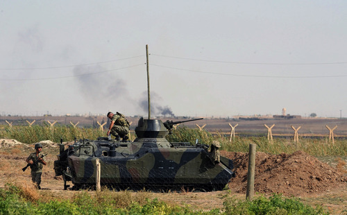 Turkish military take up positions on the Turkish side of the border near Syrian rebel-controlled town of Tel Abyad, in Akcakale, Turkey, Friday, Oct. 5, 2012. Turkey's state-run news agency says Turkish troops have returned fire after a mortar shell from Syria again landed on its territory. Turkish artillery has fired at Syrian targets for two straight days after shelling from Syria killed five civilians in Turkey. (AP Photo)