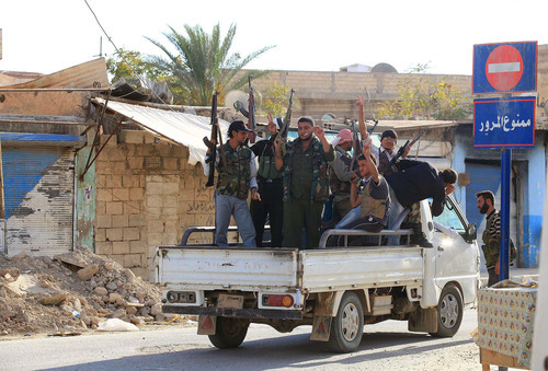 Syrian rebels ride on the back of a truck in Tel Abyad, Syria, Friday, Oct. 5, 2012.  On Friday, a Syrian mortar round hit inside Turkey, causing no injuries, and Turkish troops returned fire, the state-run news agency Anadolu said late Friday, and Turkey deployed more troops near to the border with Syria. (AP Photo)