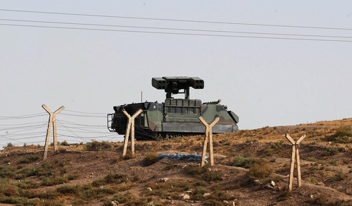 Turkish military are seen stationed near Akcakale, on the Turkish side of the border fence, running left to right, near the Syrian rebel-controlled town of Tel Abyad, Syria Friday, Oct. 5, 2012. Turkey's state-run news agency says Turkish troops have returned fire after a mortar shell from Syria again landed on its territory. Turkish artillery has fired at Syrian targets for two straight days after shelling from Syria killed five civilians in Turkey. (AP Photo)