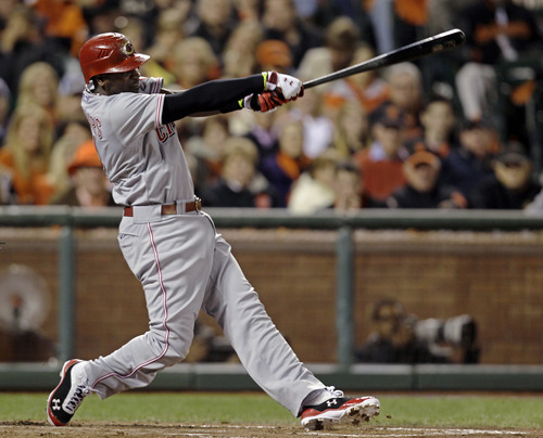 Cincinnati Reds' Brandon Phillips swings on a two-run home run in the third inning of Game 1 of the National League division baseball series against the San Francisco Giants in San Francisco, Saturday, Oct. 6, 2012. (AP Photo/Eric Risberg)