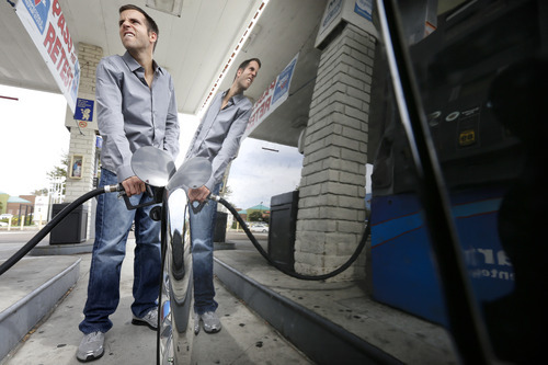 Ryan Goodman fills up his car at a gas station Friday, Oct. 5, 2012, in San Diego. Californians woke up to a shock Friday as overnight gasoline prices jumped by as much as 20 cents a gallon in some areas, ending a week of soaring costs that saw some stations close and others charge record prices. The average price of regular gas across the state was nearly $4.49 a gallon, the highest in the nation, according to AAA's Daily Fuel Gauge report. (AP Photo/Gregory Bull)