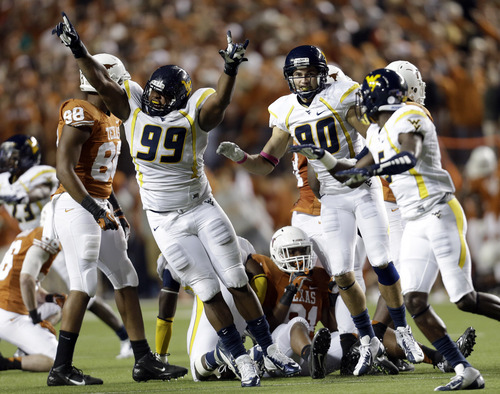 West Virginia's Desmond Jackson (99) celebrates with teammates after they forced Texas to miss a field goal-attempt during the fourth quarter of an NCAA college football game on Saturday, Oct. 6, 2012, in Austin, Texas. West Virginia won 48-45. (AP Photo/Eric Gay)