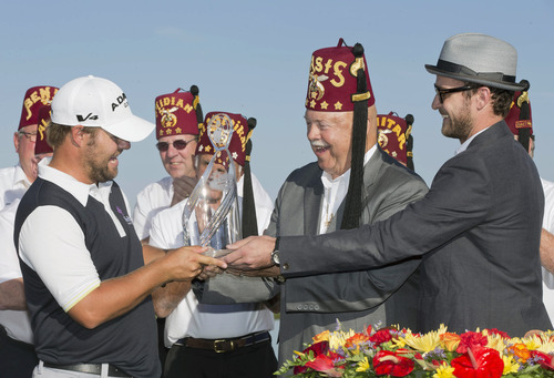 Ryan Moore, left, is presented with the championship trophy by actor/singer Justin Timberlake, right, after winning the Justin Timberlake Shriners Hospitals for Children Open golf tournament on Sunday, Oct. 7, 2012, in Las Vegas. (AP Photo/Julie Jacobson)