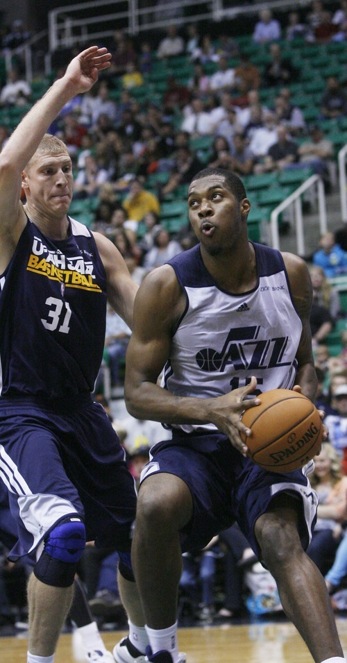 Kim Raff | The Salt Lake Tribune (right) Derrick Favors drives the basket past Brian Butch during the Jazz Scrimmage at EnergySolutions Arena in Salt Lake City, Utah on October 6, 2012.