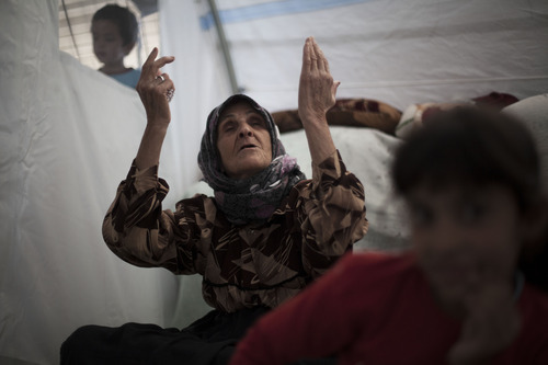 An elderly Syrian woman, who fled her home with her family due to fighting between government forces and rebels, chants,