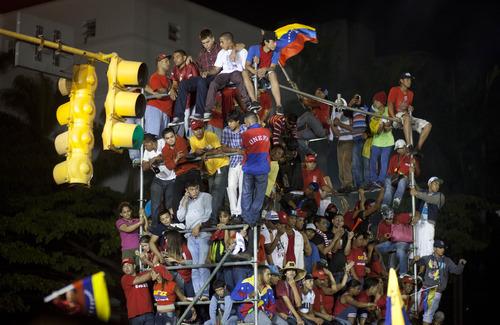 Supporters of President Hugo Chavez celebrate outside the Miraflores presidential palace  in Caracas, Venezuela, Sunday, Oct. 7, 2012. Venezuela's electoral council said late Sunday President Hugo Chavez has won re-election, defeating challenger Henrique Capriles.(AP Photo/Ramon Espinosa)