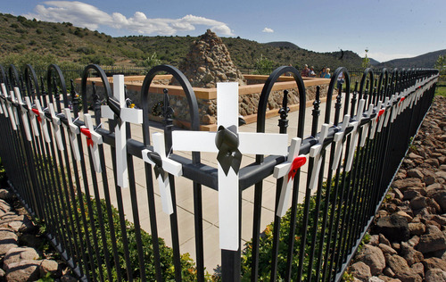 Tribune file photo Wooden crosses adorn the black wrought iron fence that surrounds the Mountain Meadows Massacre Grave Site Memorial near Enterprise.