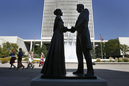 Scott Sommerdorf  |  The Salt Lake Tribune              Women on their way to the 182nd Semiannual General Conference pass by a statue of Joseph and Emma Smith outside the Church office building, Saturday, October 6, 2012.