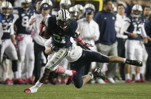 Chris Detrick  |  The Salt Lake Tribune Brigham Young Cougars running back Jamaal Williams (21) runs past Utah State Aggies safety McKade Brady (36) during the second half of the game at LaVell Edwards Stadium Friday October 5, 2012. BYU won the game 6-3.