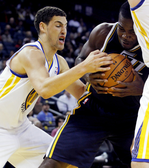 Utah Jazz's Paul Millsap, right, struggles for the ball with Golden State Warriors' Klay Thompson during a preseason NBA basketball game in Oakland, Calif., Monday, Oct. 8, 2012. (AP Photo/George Nikitin)