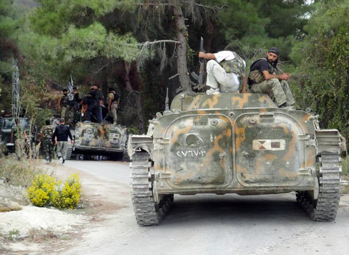 In this Sunday October 7, 2012 citizen journalism image provided by Edlib News Network, ENN,  which has been authenticated based on its contents and other AP reporting, Free Syrian Army fighters on top of armored vehicles that were captured from the Syrian Army in the village off Khirbet al-Jouz, in the northern province of Idlib, Syria. The Turkish state-run Anadolu news agency said Sunday that the rebels had regained full control of Khirbet al-Jouz. (AP Photo/Edlib News Network ENN)