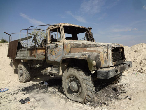 In this Sunday, Oct. 7, 2012 citizen journalism image provided by Edlib News Network, ENN, which has been authenticated based on its contents and other AP reporting, a burned Syrian Army military truck is seen in the village of Khirbet al-Jouz, in the northern province of Idlib, Syria. The Turkish state-run Anadolu news agency said Sunday that the rebels had regained full control of Khirbet al-Jouz. (AP Photo/Edlib News Network, ENN)