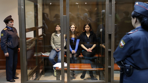 Feminist punk group Pussy Riot members, from left, Maria Alekhina, Yekaterina Samutsevich and Nadezhda Tolokonnikova sit in a glass cage at a court room in Moscow, Wednesday. Oct. 10, 2012.  On Wednesday, Samutsevich unexpectedly walked free from a Moscow courtroom, but the other two now head toward a harsh punishment for their irreverent protest against President Vladimir Putin: a penal colony. (AP Photo/Sergey Ponomarev)