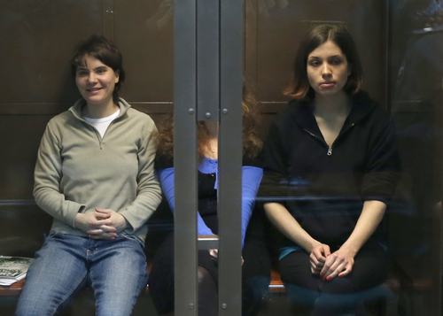 Feminist punk group Pussy Riot members, from left, Maria Alekhina, Yekaterina Samutsevich and Nadezhda Tolokonnikova sit in a glass cage in a court room in Moscow, Wednesday. Oct. 10, 2012.  On Wednesday, Samutsevich unexpectedly walked free from a Moscow courtroom, but the other two now head toward a harsh punishment for their irreverent protest against President Vladimir Putin: a penal colony. (AP Photo/Sergey Ponomarev)