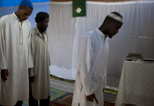 In this Sept. 28, 2012 photo, Muslim men stand during Friday prayer service at the Al-Fattah Mosque in Gressier, Haiti.  Islam has won a growing number of followers in this impoverished country, especially after the catastrophic earthquake in 2010 that killed hundreds of thousands and left millions more homeless. (AP Photo/Dieu Nalio Chery)