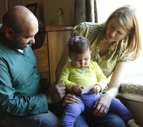 Leah Hogsten  |  The Salt Lake Tribune Naveen and Autumn Pammi, of North Salt Lake, watch as their 13-month-old daughter, Leela, points to a photo of their dog Rusty, who died within minutes from inhaling a herbicide that was being sprayed at the neighbor's home in August. Rusty inhaled the chemical 2-4-D, or Dichlorophenoxyacetic acid. The incident has prompted the couple to speak up about the dangers of pesticides and support another valley resident's efforts to get Utah to adopt a neighbor notification law.