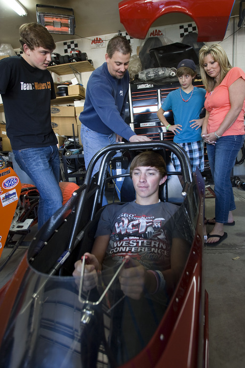 Scott Sommerdorf  |  The Salt Lake Tribune              Jake Jones, 15, left, father Tim, Jarred, 12, and their mother, Jill Jones of West Jordan stand by as Tim works with engine adjustments while Josh Jones sits in the cockpit of the racer he will pilot in Memphis at the IHRA World Finals Oct 12-14. There are only 16 kids nationwide that were selected. Tim & Jill Jones of West Jordan and their 3 sons Josh (17) Jake (15) and Jared (12) race at Rocky Mountain Raceways. Photographed in the family workshop, Sunday, October 7, 2012.