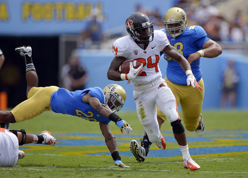 Oregon State running back Storm Woods, center, runs the ball as UCLA safety Andrew Abbott, left, tries to tackle him and nose tackle Seali'i Epenesa gives chase during the first half of their NCAA college football game, Saturday, Sept. 22, 2012, in Pasadena, Calif. AP Photo/Mark J. Terrill)