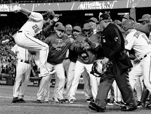 Washington Nationals' Jayson Werth, top left, leaps toward home plate to be greeted by teammates after hitting the game-winning solo home run in the ninth inning of Game 4 of the National League division baseball series against the St. Louis Cardinals on Thursday, Oct. 11, 2012, in Washington. Washington won 2-1. (AP Photo/Alex Brandon)