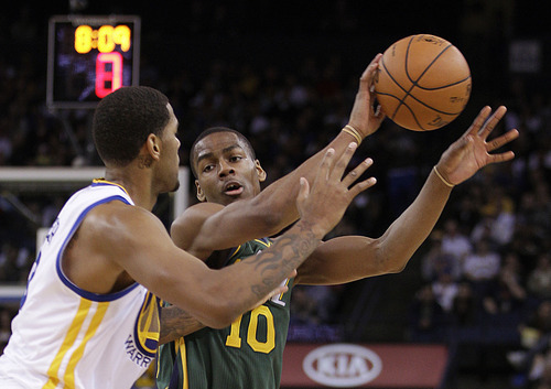 Utah Jazz guard Alec Burks (10) passes away from Golden State Warriors' Jeremy Tyler during the first half of an NBA basketball game Thursday, Feb. 2, 2012, in Oakland, Calif. (AP Photo/Ben Margot)