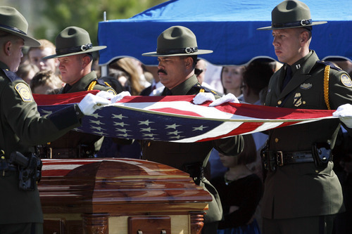 Francisco Kjolseth  |  The Salt Lake Tribune U.S. Customs and Border Patrol agents fold the flag over the casket containing border patrol agent Nicholas Ivie after arriving at the Spanish Fork Cemetery surrounded by friends, family, and numerous service agencies on Thursday, October 11, 2012.