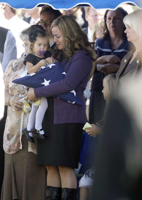 Francisco Kjolseth  |  The Salt Lake Tribune Christy Ivie holds her daughter Presley, 22-months, after receiving the flag in honor of her husband, border patrol agent Nicholas Ivie, a Provo native, during funeral services at Spanish Fork cemetery on Thursday October 11, 2012. Ivie was killed on Oct. 2 near the Arizona-Mexico border in what investigators deemed was a friendly fire accidental shooting.