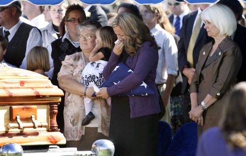 Francisco Kjolseth  |  The Salt Lake Tribune Christy Ivie is overcome with emotion after receiving the flag in honor of her husband, border patrol agent Nicholas Ivie, a Provo  native, during funeral services at Spanish Fork cemetery on Thursday October 11, 2012. Ivie was killed on Oct. 2 near the Arizona-Mexico border in what investigators deemed was a friendly fire accidental shooting.