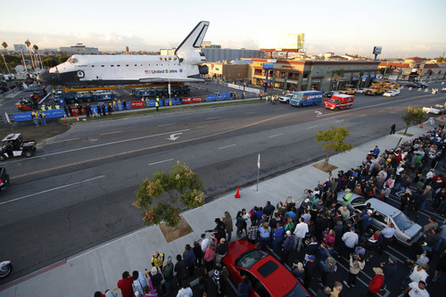 Spectators gather to watch the space shuttle Endeavour in Los Angeles, Friday, Oct. 12, 2012. Endeavour's 12-mile road trip kicked off shortly before midnight Thursday as it moved from its Los Angeles International Airport hangar en route to the California Science Center, its ultimate destination, said Benjamin Scheier of the center. (AP Photo/Jae C. Hong)