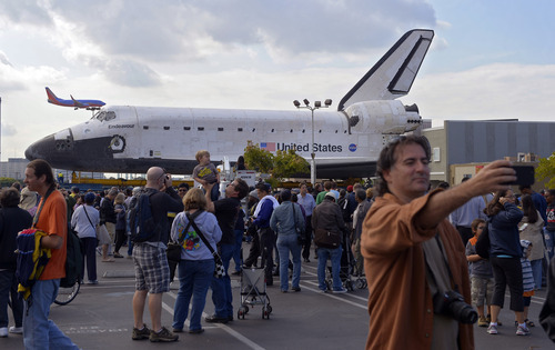 Spectators gather around the Space Shuttle Endeavour before it is moved along city streets, Friday, Oct.12, 2012, in Los Angeles.  Endeavour's two-day, 12-mile road trip to the California Science Center, where it will be put on display,  kicked off early Friday. Rolled on a 160-wheeled carrier, it left from a hangar at the Los Angeles International Airport, passing diamond-shaped