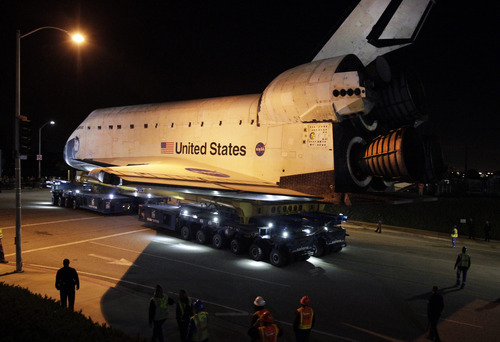 Space shuttle Endeavour leaves Los Angeles International Airport hangar onto the streets in Los Angeles on Friday, Oct. 12, 2012. Endeavour's 12-mile road trip kicked off shortly before midnight Thursday as it moved from its Los Angeles International Airport hangar en route to the California Science Center, its ultimate destination, said Benjamin Scheier of the center. (AP Photo/Los Angeles Times, Lawrence K. Ho)