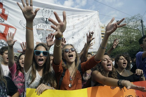 High school children protest outside the finance ministry against state funding cuts to municipalities that have disrupted school bus services, in Athens on Thursday, Oct. 11, 2012. Greece's coalition government is struggling to meet demands by international rescue creditors for a massive new austerity cuts required for continued payment of emergency loans.  (AP Photo/Dimitri Messinis)