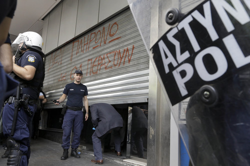 Riot police stand by as a man ducks under lowered shutters at the entrance of the finance ministry, in Athens on Thursday, Oct. 11, 2012. Writing on the shutters reads: