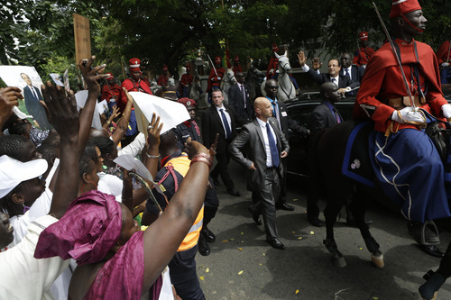 French President Francois Hollande, upper right, and Senegalese counterpart Macky Sall wave to supporters lining the streets as they arrive at the Presidential Palace in Dakar, Senegal, Friday, Oct. 12, 2012. Hollande was on a one-day visit to Senegal Friday, en route to Kinshasa, Congo for the Francophonie Summit. (AP Photo/Rebecca Blackwell)