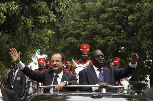 French President Francois Hollande, left, and Senegalese counterpart Macky Sall wave to supporters lining the streets as they arrive at the Presidential Palace in Dakar, Senegal, Friday, Oct. 12, 2012. Hollande will attempt to repair France's relationship with Africa on his first visit to the continent on Friday, beginning with a stop in Senegal, the seat of France's former colonial empire. He is set to leave Friday night for Congo, where he will attend the Francophonie summit in the capital, Kinshasa.(AP Photo/Rebecca Blackwell)