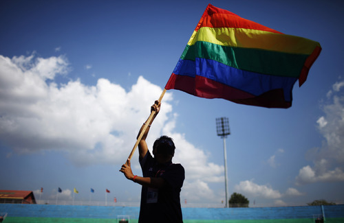 A member of the Lesbian, Gay, Bisexual and Transgender (LGBT) community waves a gay pride flag during the opening ceremony of the 1st South Asian LGBT Games organized by Blue Diamond Society in Katmandu, Nepal, Friday, Oct. 12, 2012. According to Sunil Babu Pant, first openly gay politician in Nepal and head of Blue Diamond Society, around 250 LGBT community members are participating in the festival. (AP Photo/Niranjan Shrestha)