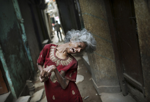 A severely disabled Indian woman begs for change in an alleyway in New Delhi, India, Friday, Oct. 12, 2012. (AP Photo/Kevin Frayer)