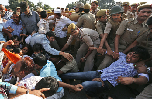 India Against Corruption (IAC) activists are carried away by policemen as they sit with disabled people to protest against alleged embezzlement of government funds meant for the welfare of the disabled, in New Delhi, India, Friday, Oct. 12, 2012. The activist alleged financial irregularities in a trust run by Indian Law Minister Salman Khurshid and his wife Louise Khurshid and demanded the resignation of Khurshid and a case be registered against him, according to a news agency. (AP Photo/Saurabh Das)