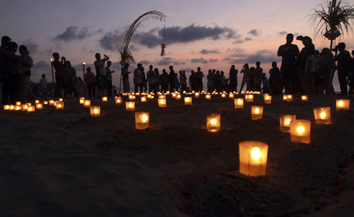 People light candles at a beach during a memorial service to mark the 10th anniversary of the terrorists attacks, in Kuta, Bali, Indonesia, Friday, Oct. 12, 2012. A decade after twin bombs killed scores of tourists partying at two beachfront nightclubs on Indonesia's resort island of Bali, survivors and victims' families on Friday braved a fresh terrorism threat to remember those lost to the tragedy. (AP Photo/Firdia Lisnawati)