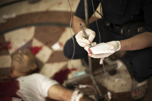 In this Thursday, Oct. 11, 2012 photo, a Syrian doctor notes the name of a severely wounded man at Dar al-Shifa hospital in Aleppo, Syria. (AP Photo/Manu Brabo)
